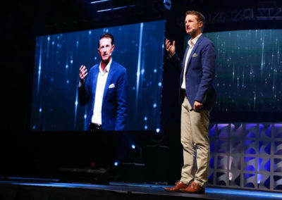 photo of MIchael Crossland presenting on stage with one arm raised
