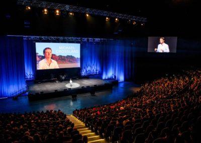 photo of Michael Crossland presenting to large auditorium